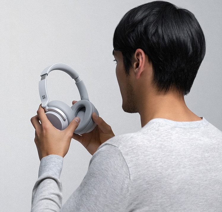 Ein Mann hält Surface Headphones