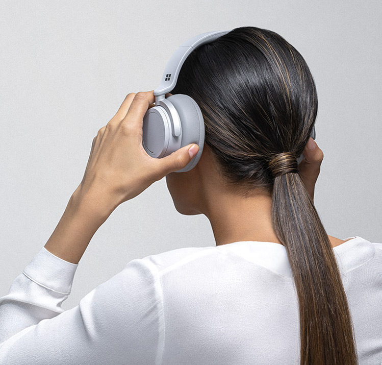 A woman puts Surface Headphones on her head