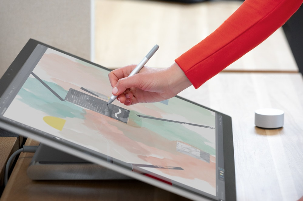 Person skriver på Surface Studio 2-datamaskinen med Surface-penn