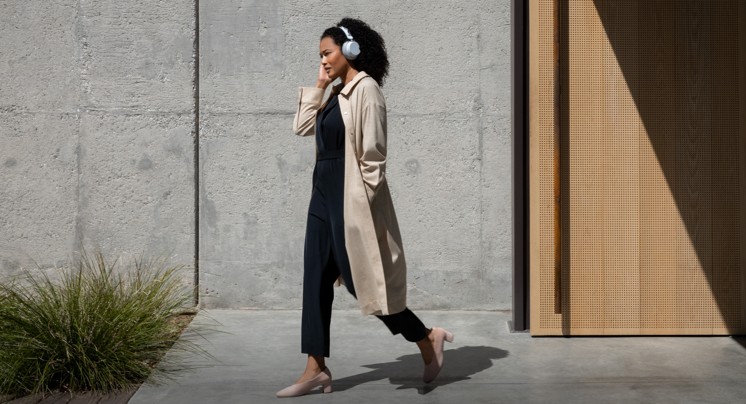 A woman walking with Surface Headphones on her head
