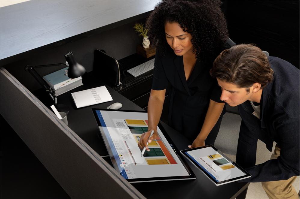 Kaksi ihmistä käyttämässä Surface-tietokoneita studiotilassa
