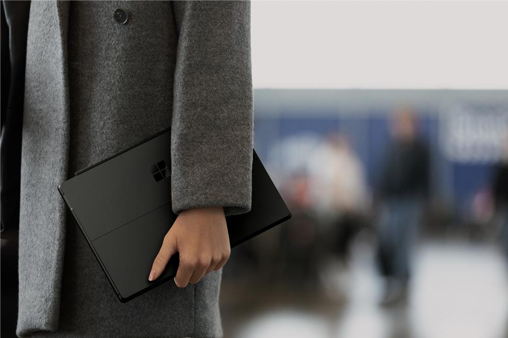 En kvinna i en svart ullkappa håller en svart Surface Pro 6