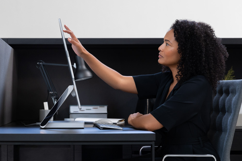 Woman touching the Surface Studio 2 screen