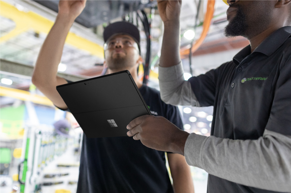 Due persone collaborano, una di esse digita sul computer Surface Pro 6