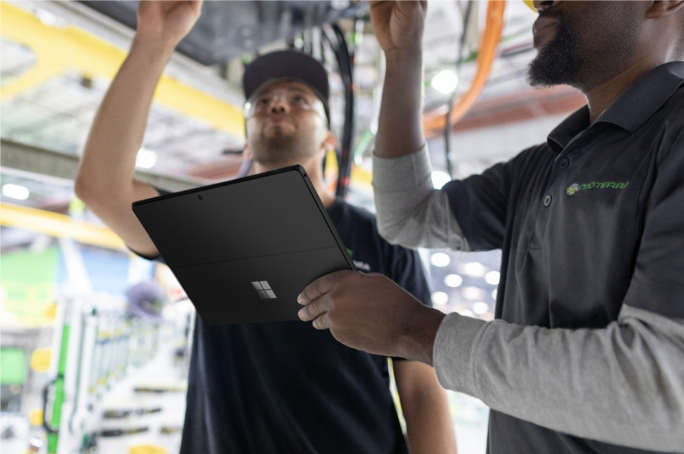 Two people collaborating while one types on the Surface Pro 6.