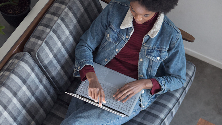 En person skriver på skärmen på en Surface Laptop 2