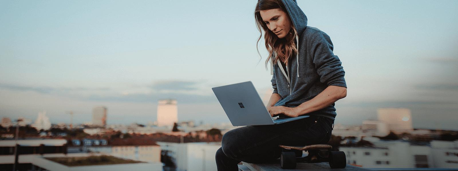 Eine Frau sitzt auf einem Longboard und nutzt ihren Laptop