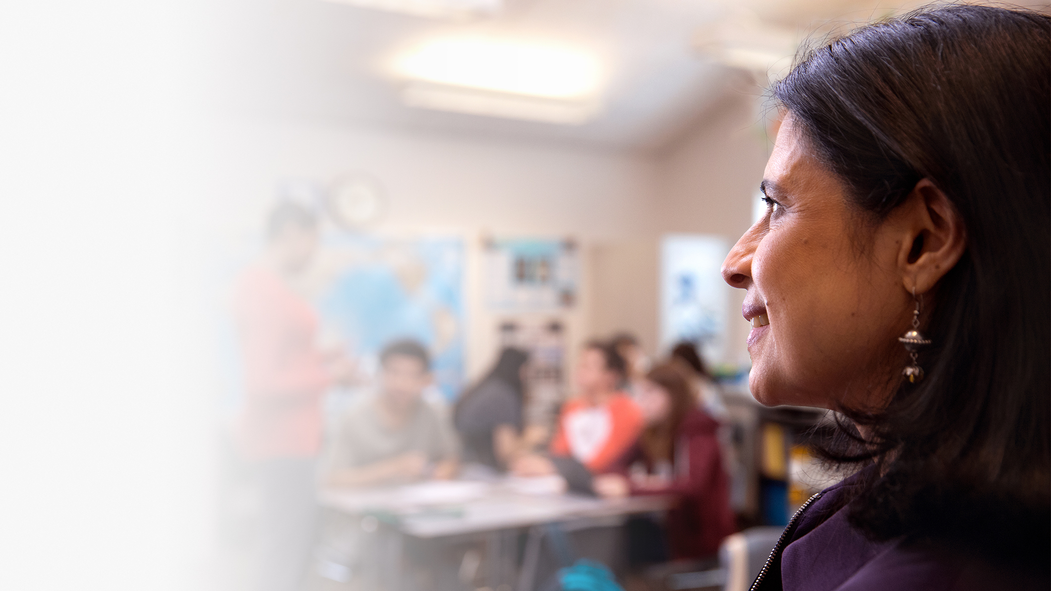 A woman looks at a classroom with teen students.