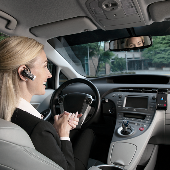 Photograph of a person in a car on a phone call using a wireless headset.