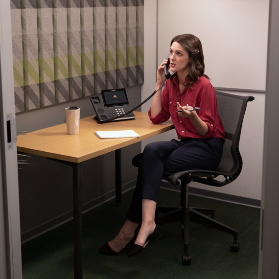 Photograph of a person on a phone call in a phone room.