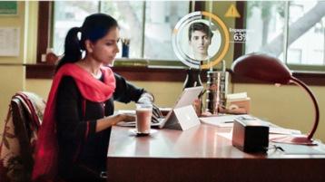 Eine junge Frau arbeitet an einem Tablet und profitiert von KI.