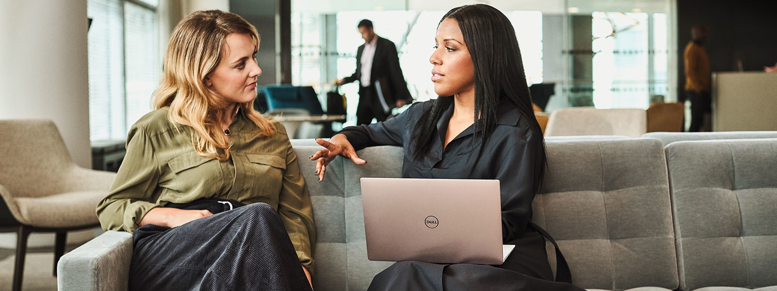Two business women in conversation on a couch