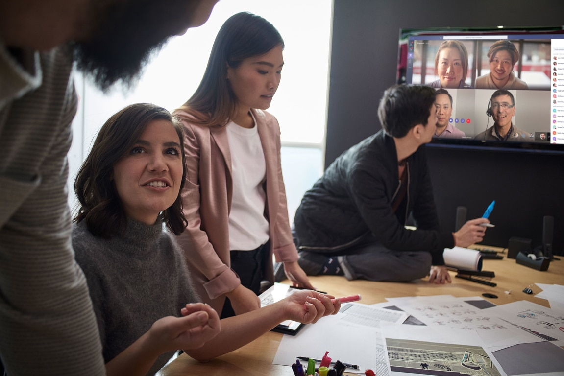 Group of coworkers chatting with a video-calling system in the background