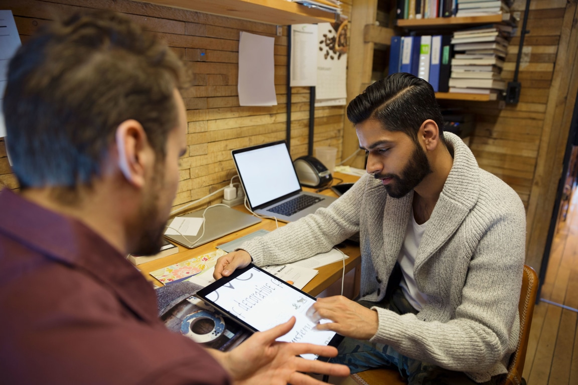 Two men in a back office, looking at a tablet with data