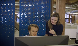 Still image from video of two people looking at a large display monitor on a desk in a large open office, one is standing and motioning at information on the screen, the other is seated and looking at the screen