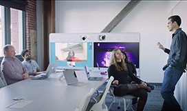 Still image from video of a group of people seated in a conference room listening to a person standing and speaking