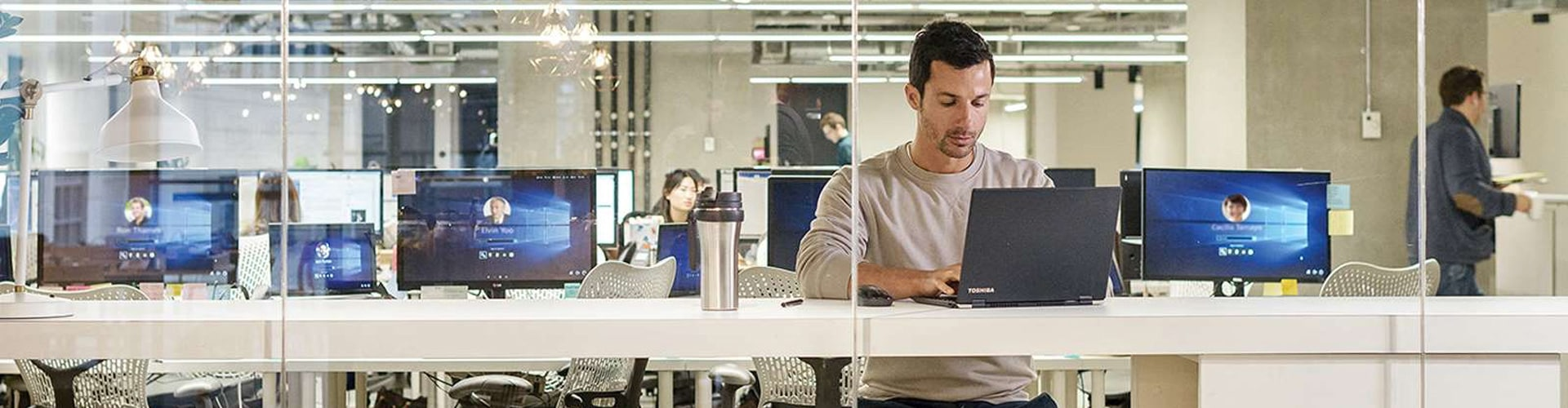 Person sitting at counter in office working on laptop
