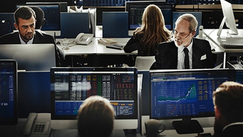 Financial services professionals viewing data charts on monitors in control room setting