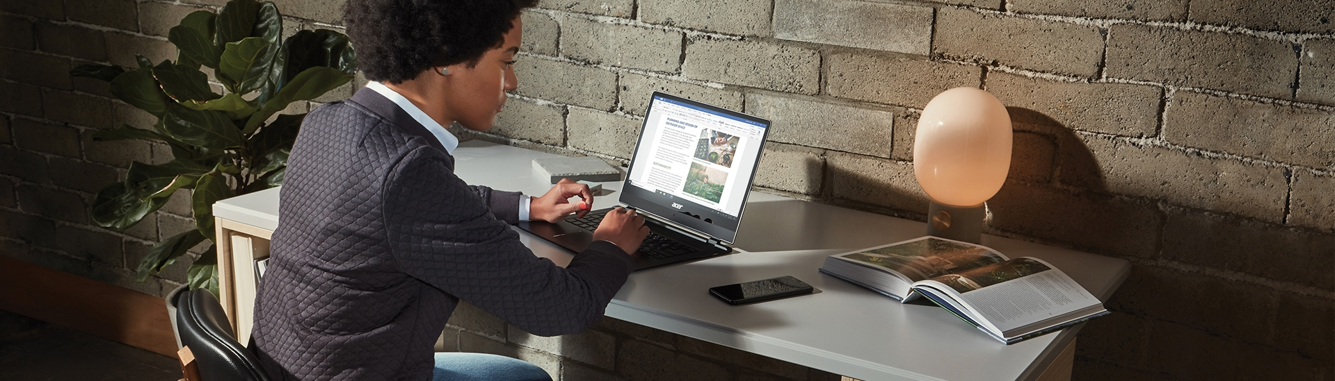Photograph of a person seated at a desk working on a laptop. Also on the desk is a mobile device, an open book, and a decorative lamp.