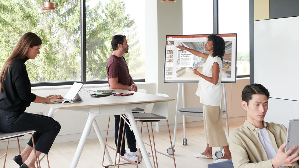 People gather around a Surface Hub 2S in an open meeting space