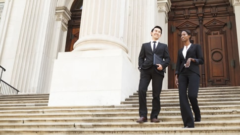 Two business professionals walking down the steps of a large government building