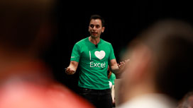 "Male speaker with green ""I-love-Excel"" t-shirt standing on stage speaking to the audience."