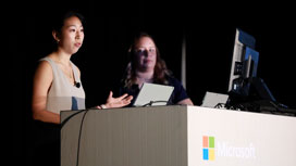 Megan Longoria and Tessa Hurr standing behind a podium talking about creating accessible Power BI reports.