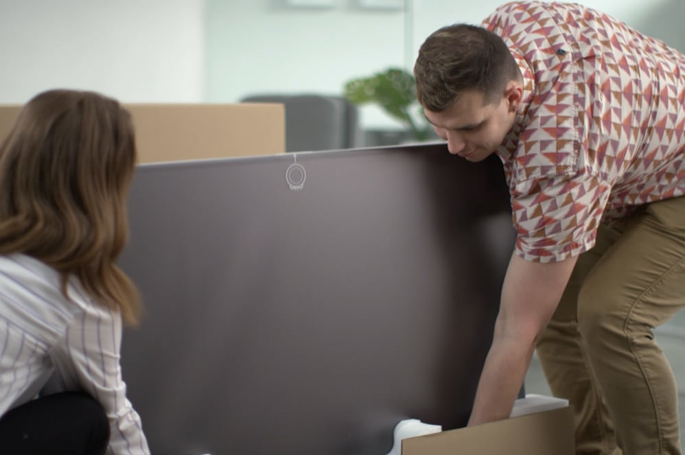 Two people lift a Surface Hub 2S together