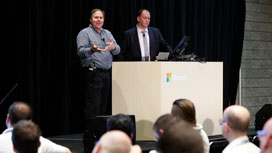 Kyle Young and Ben Vollmer standing behind a speaker's podium on stage talking about what's next for Dynamics 365 for Field Service.
