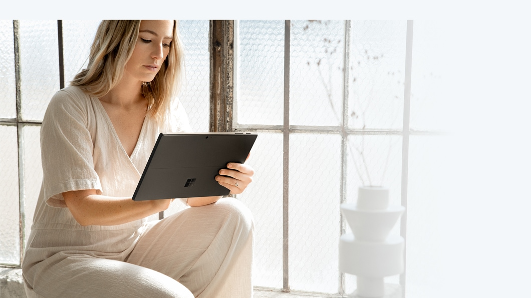 Woman working on black Surface Pro 6