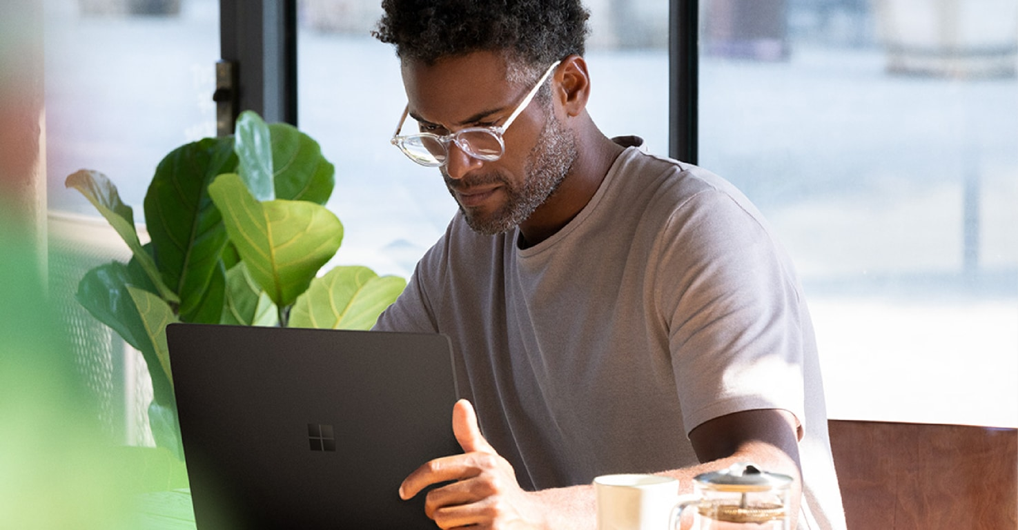 Photograph of a person seated in a café working on a Surface Book 2