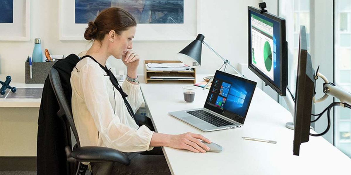Person working at desk on a Windows 10 laptop