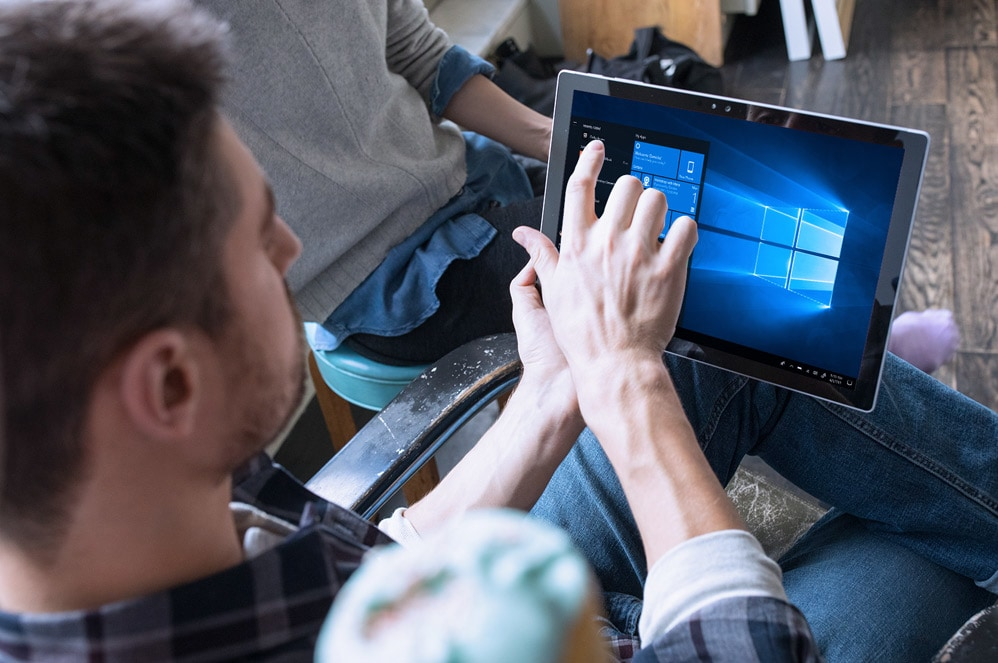 A man uses the touchscreen on his Surface Pro to interact with the Windows Start menu