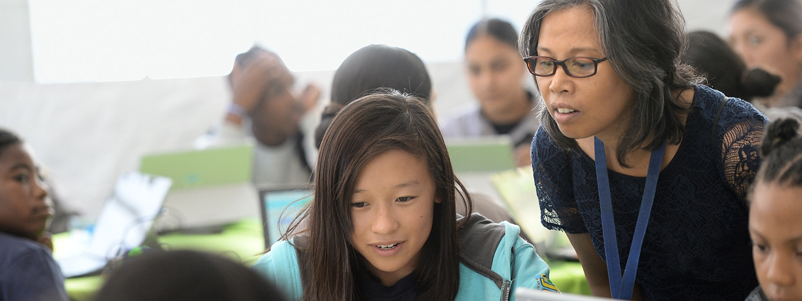 A teacher leans in to help a student working on a Microsoft Surface tablet.