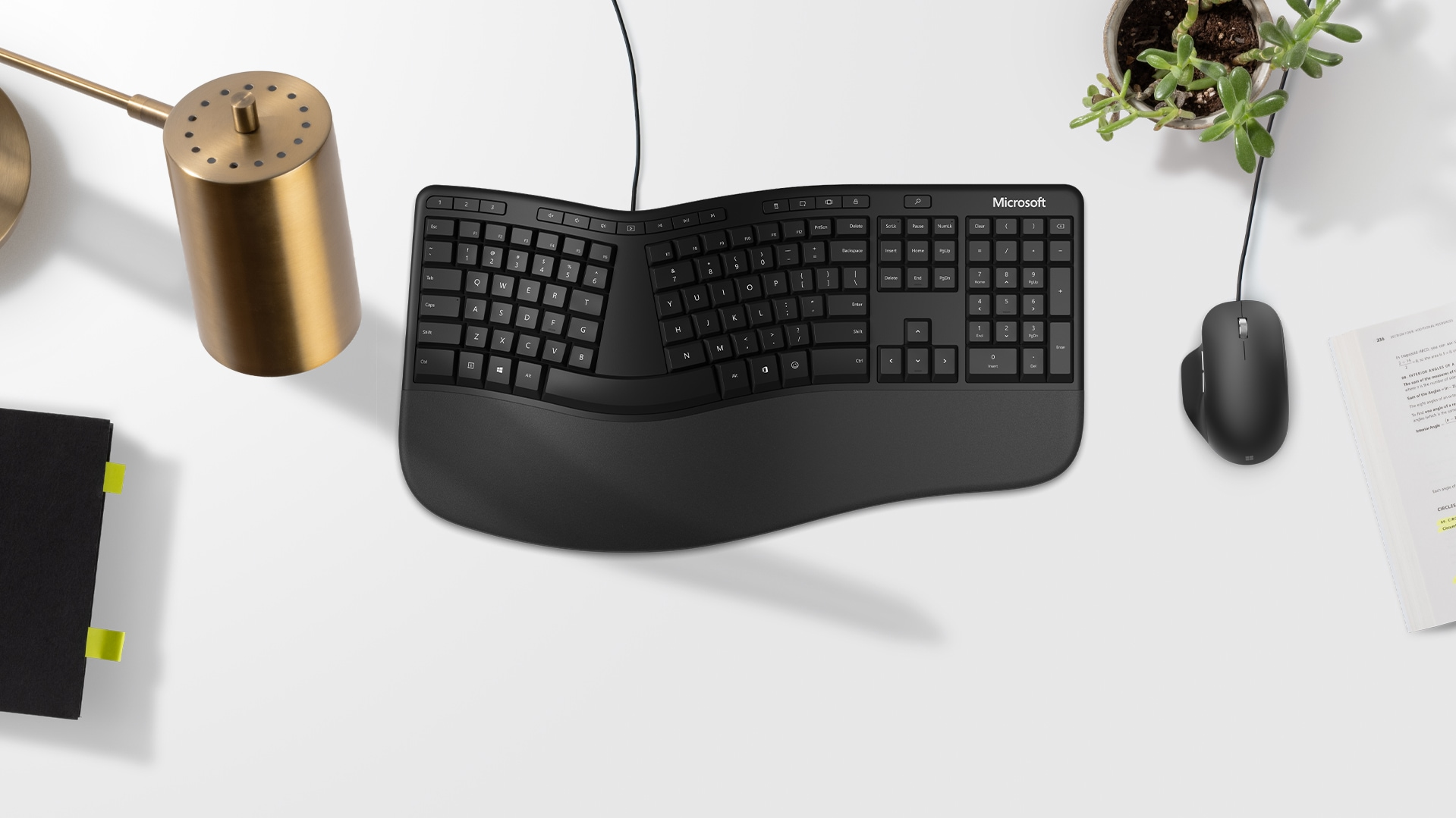 A Microsoft Ergonomic Keyboard and a Precision Mouse sit on a desk.