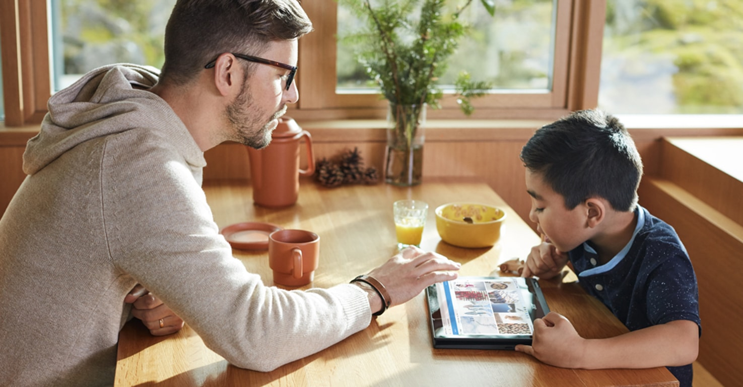 A parent and child sitting at a breakfast table looking at a tablet device