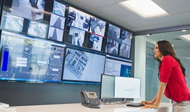 Person standing at a desk looking at surveillance images on a bank of large, wall-mounted displays