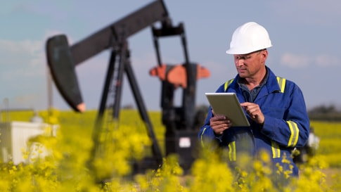 Male energy professional wearing hardhat using tablet while standing in front of an oil derrick