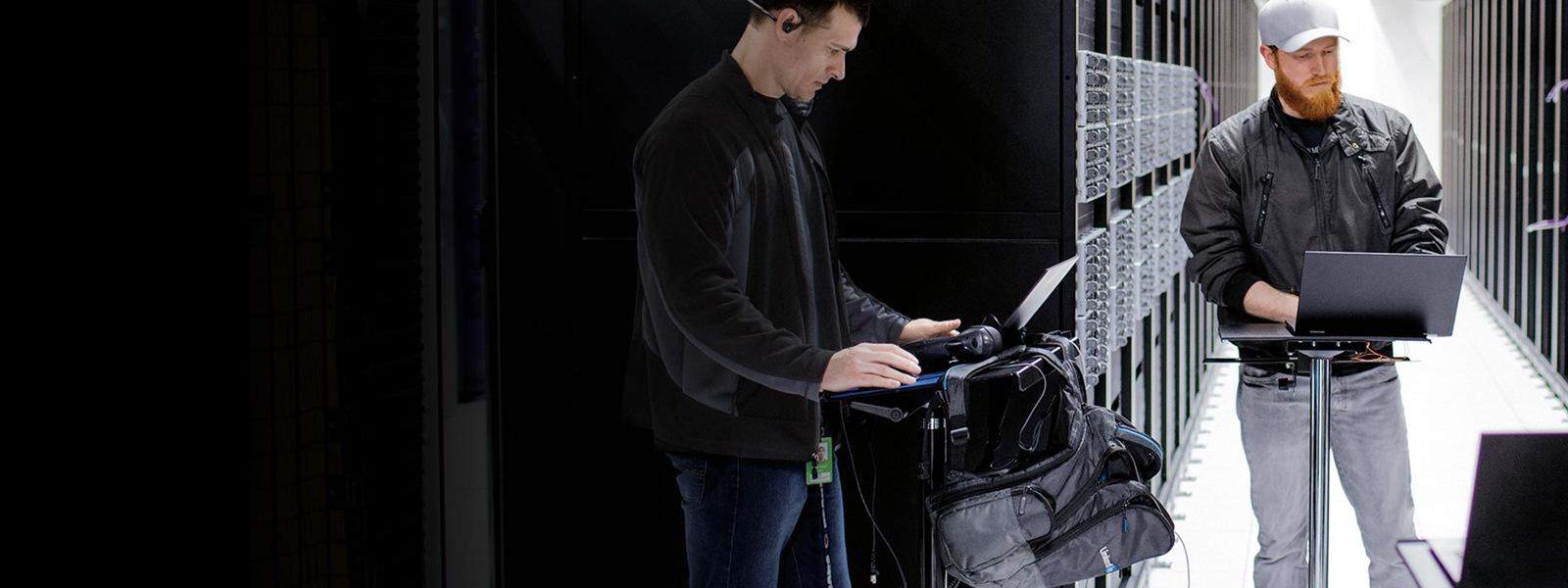 Zwei Männer stehen inmitten eines Serverraums und lesen Daten von ihren Laptops ab.