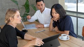 Drei junge Menschen sitzen an einem Schreibtisch und sehen sich etwas auf einem Surface an.