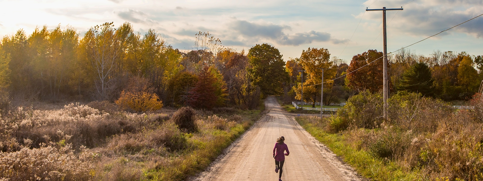 A woman jogs along on an unpaved rural road lined with trees and utility poles.