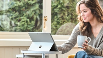 Person holding a coffee cup seated at a small table using a Surface Pro 6