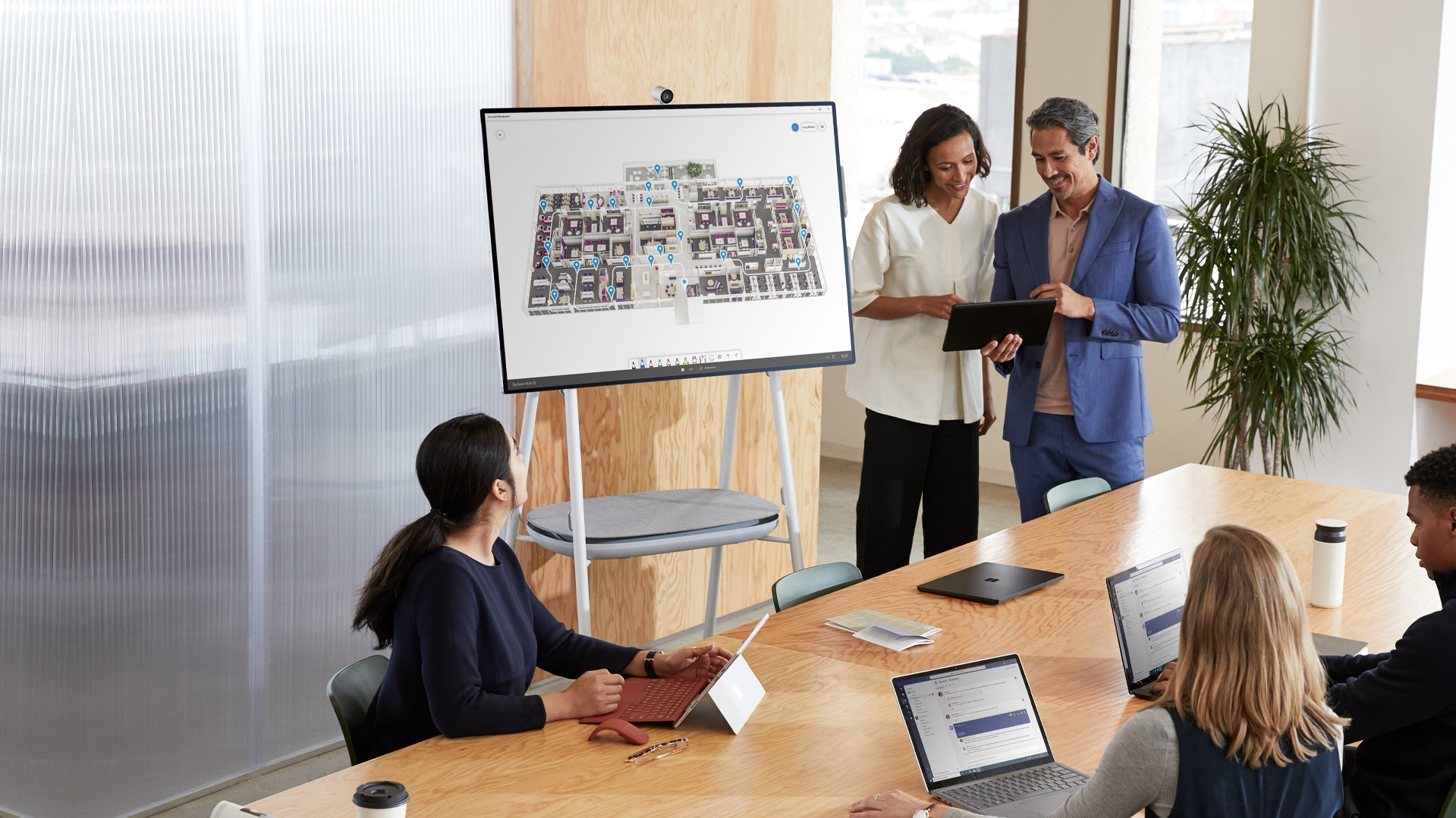 Colleagues gather in conversation in a room with several personal Surface devices and Surface Hub 2S
