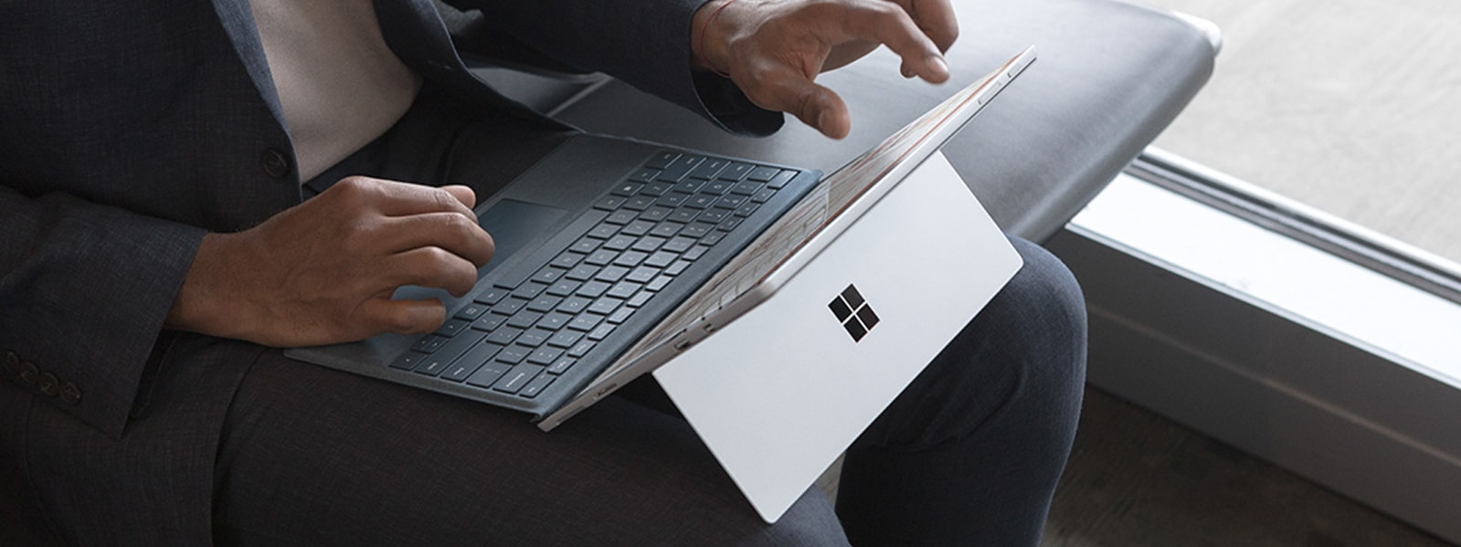 A man uses his Surface Pro and Surface Pro Signature Type Cover in Ice Blue