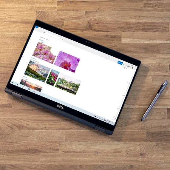 Dijital kalemle ahþap bir masaya oturan bir Windows 10 2'si 1 arada bilgisayar.