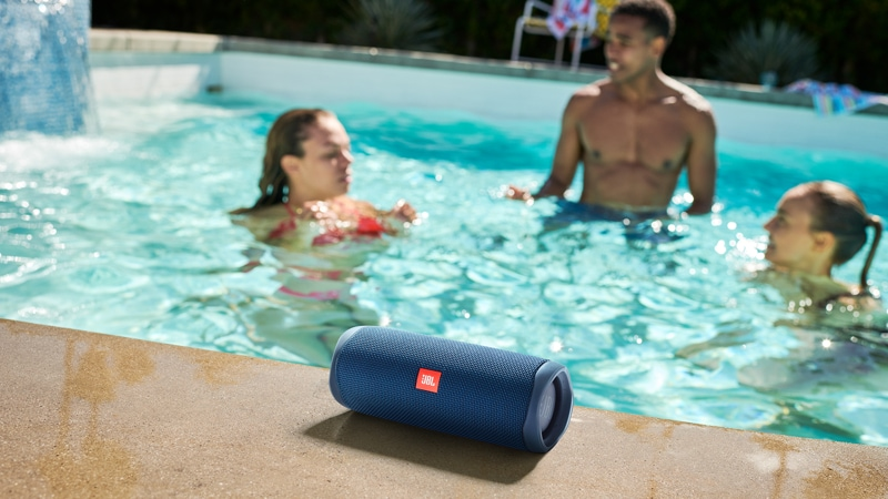 Three people in a swimming pool with a JBL FLIP 5 speaker on the edge of the pool