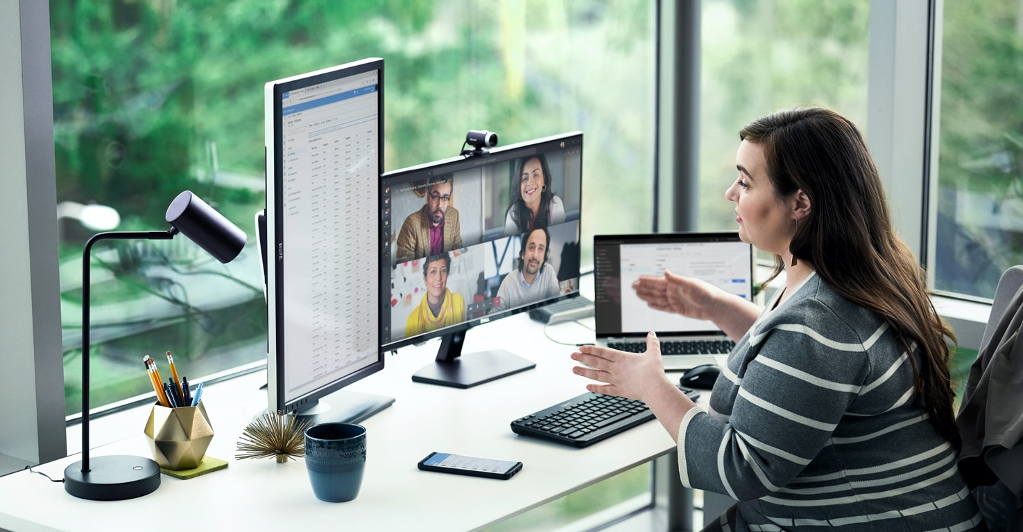 A woman works at a desk with multiple computer monitors while video conferencing with coworkers