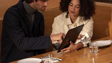 Zwei Personen arbeiten auf einem neuen Surface Pro X für Unternehmen zusammen.