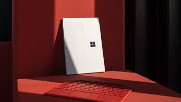 A new Surface Pro 7 for Business and a red mouse.