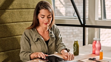 A person sitting alone using a tablet.